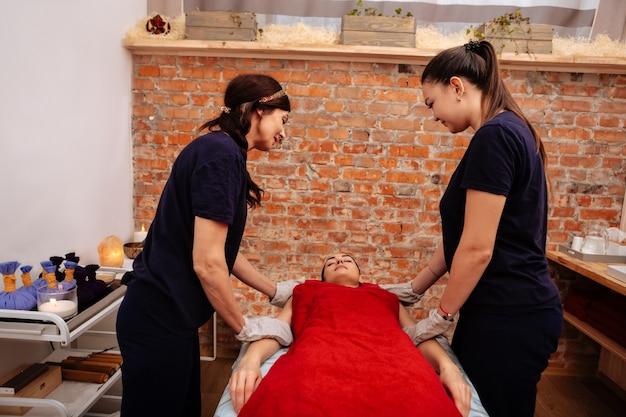Оборудованный спа кабинет. трудолюбивые массажистки в черной униформе в специальных перчатках вытирают клиента на кровати