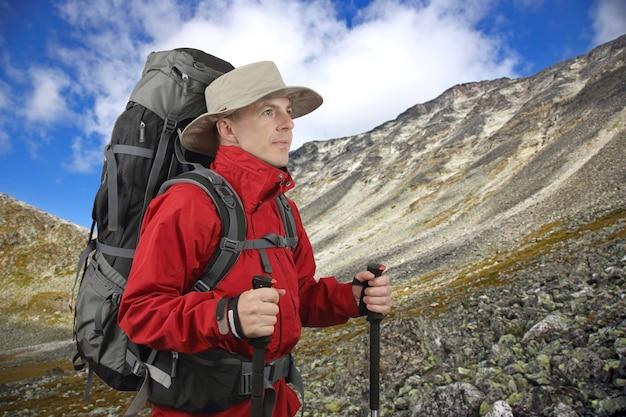 먼 곳을 바라 보는 하이킹 폴과 함께 빨간 재킷을 입은 여행자를 장비