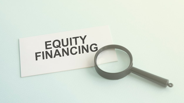 Equity financing word on white paper card and magnifying lens