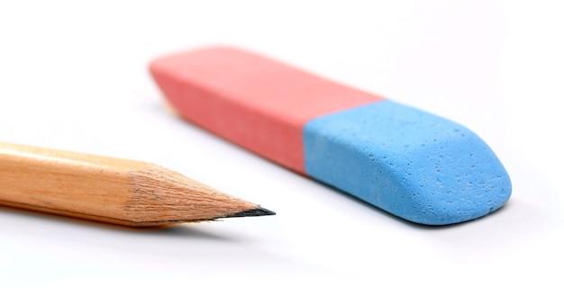 Ластик и карандаш на белом столе.
