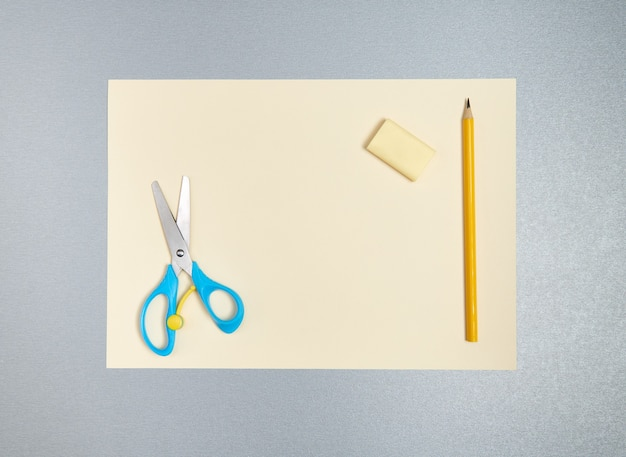 Ластик, карандаш, ножницы на желтом листе бумаги. вид сверху, плоская лежала на сером фоне
