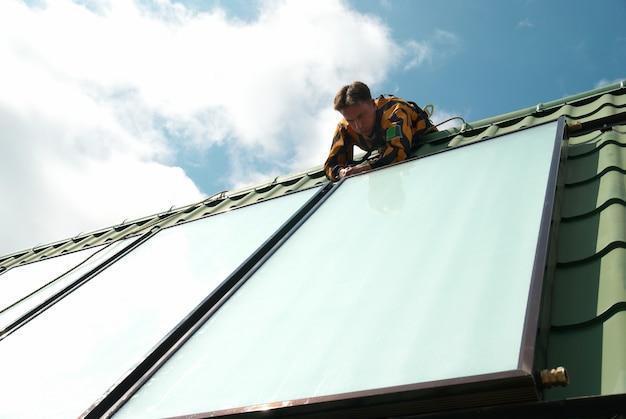 Монтажник солнечной системы водяного отопления на крыше.