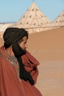 砂漠、erg chigagaラグジュアリー砂漠キャンプ、サハラ砂漠、モロッコに立っている男