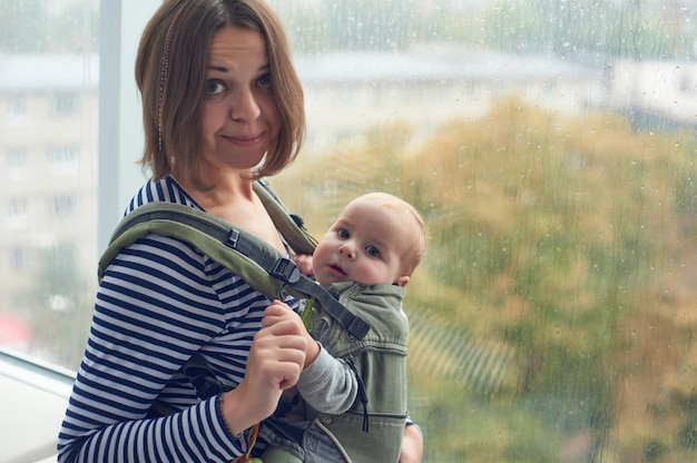 Мать с ergobaby нося малыша дома.