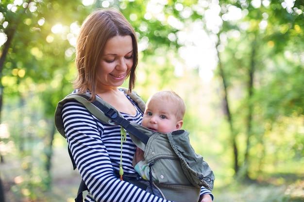 Мать с ergobaby, перевозящих малыша в лесу