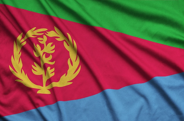 Eritrea flag is depicted on a sports cloth fabric with many folds.