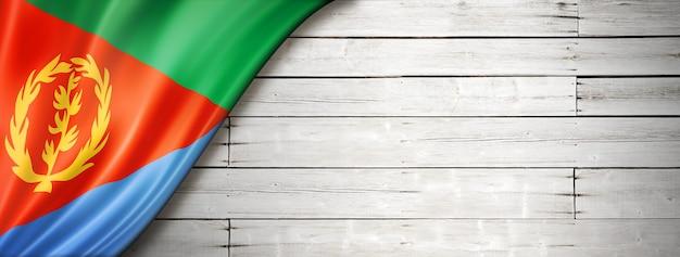 Флаг эритреи на старой белой стене. горизонтальный панорамный баннер.