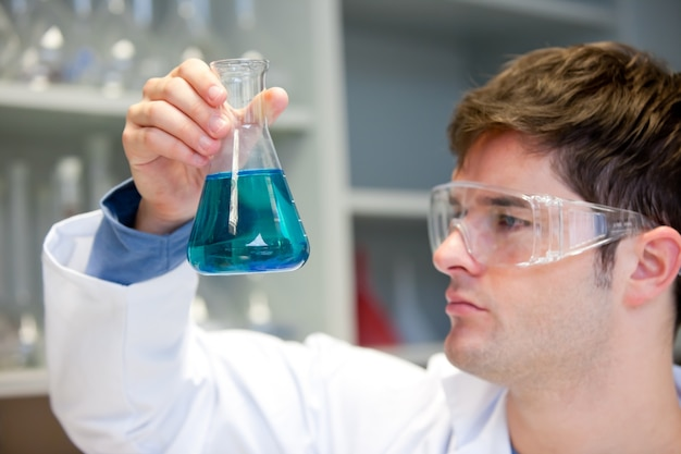 Молодой ученый, глядя на жидкость в erlenmeyer