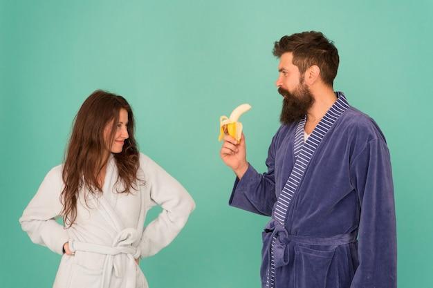 カップルのためのエロティックなゲーム。愛の青い背景のカップル。官能的なカップル。セクシーな女性はバナナを食べるひげを生やした男を見てください。フェラチオと欲望。メンズの健康と効力。家庭服の家族のカップル。