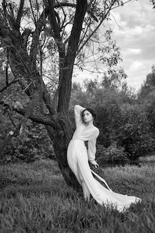 Эротичная молодая женщина в длинном белом платье гуляет в весеннем парке у реки. сексуальная брюнетка позирует на природе