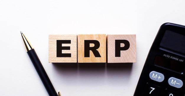 電卓とペンの近くの明るい背景の木製の立方体に書かれたerp。ビジネスコンセプト