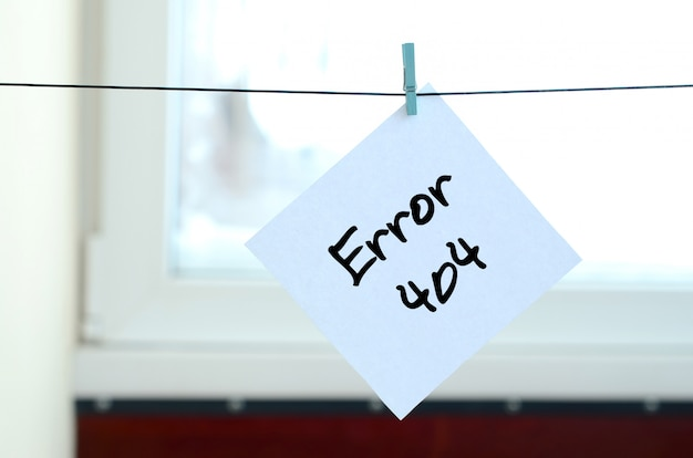Error 404. note is written on a white sticker that hangs with a clothespin on a rope