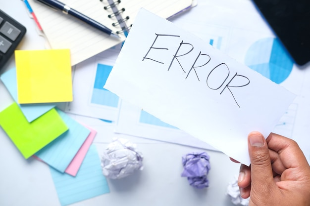 Error word on paper with notepad and chart on table