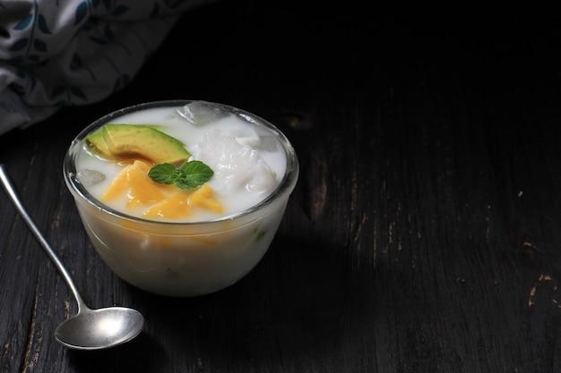 Es teler, 달콤한 코코넛 물과 연유에 열대 과일 칵테일의 전통적인 인도네시아 아이스 디저트. 복사 공간이 있는 그릇에 제공