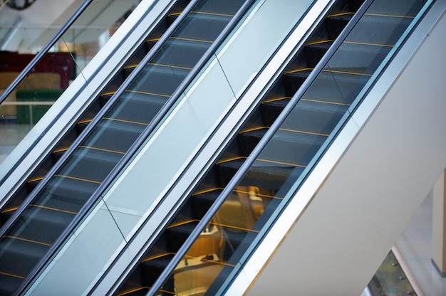Escalator and empty modern shopping mall interior