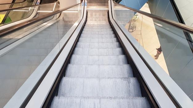 쇼핑몰의 에스컬레이터. 쇼핑 센터 내부에 있는 추상 은색 에스컬레이터. 콘크리트 벽 배경입니다. 전송 개념입니다.