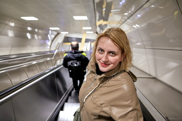An escalator moves down to an underground metro station young white woman descends while standing on steps