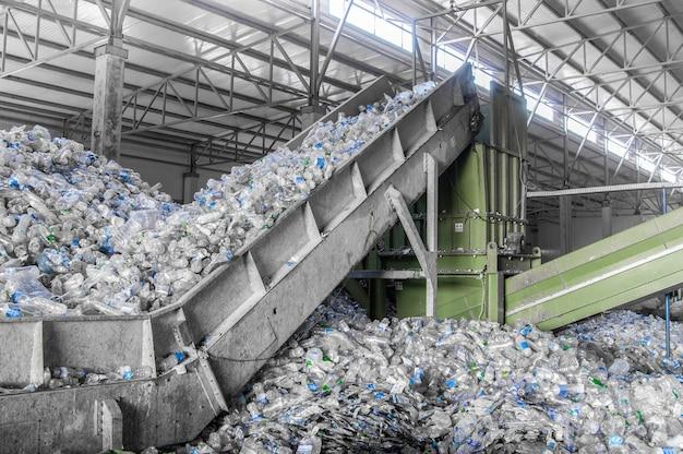 Эскалатор с кучей пластиковых бутылок на заводе по переработке и переработке