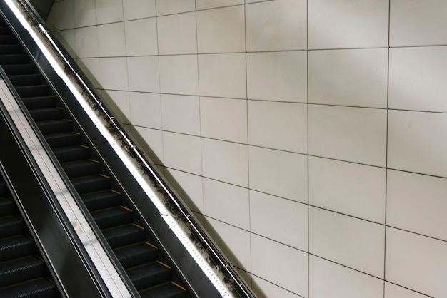 Escalator with blank tiled wall