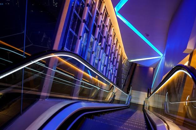 Эскалатор со светодиодной подсветкой рядом с технологией абстрактной неоновой красочной световой темой.
