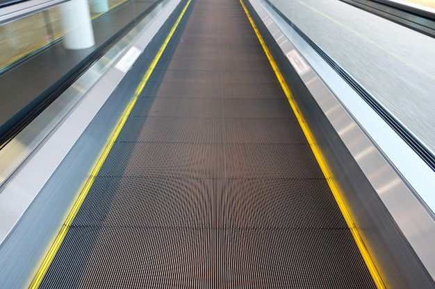 空港で前方に移動するエスカレーターの黄色い帯