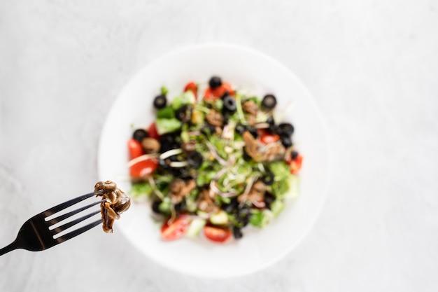 흰색 바탕에 그린 샐러드 근처 포크에 escargot 포도 달팽이. 프랑스 미식가 요리.