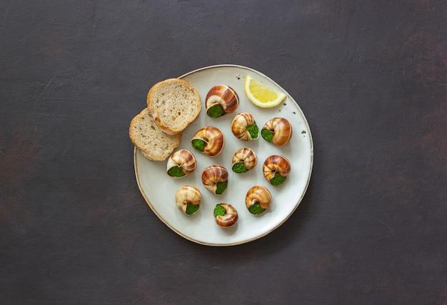 エスカルゴドブルゴーニュ。カタツムリとハーブバター。健康的な食事。フランス料理。