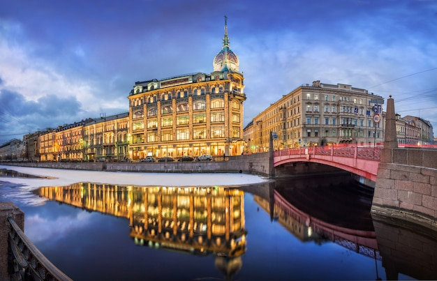 Esders and scheufals store building and reflection in the water of the moika river in st. petersburg