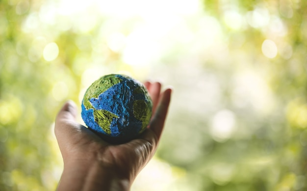 Esg, world earth day concept. green energy, renewable and sustainable resources. environmental and ecology care. hand holding a handmade globe in nature