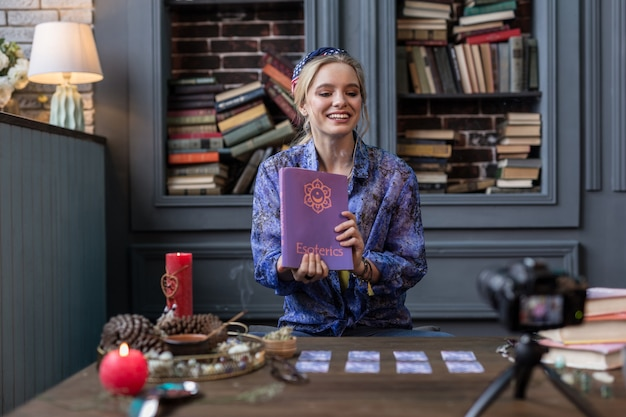 難解な科学。カメラの前に座っている間難解な本を持っている素敵なポジティブな女性