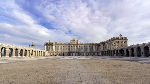 Esplanade and large courtyard of the royal palace of madrid at sunrise on a day with blue sky and clouds. spain.