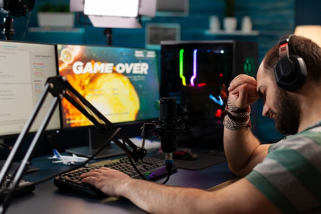 헤드폰이 있는 e스포츠 스트리머는 현대적인 그래픽 라이브 챔피언십으로 공간 사수 비디오 게임을 잃습니다. 기술 네트워크 무선을 사용하여 게임 토너먼트 중 온라인 스트리밍 사이버 수행