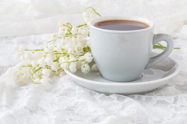 Espresso and bouquet of flowers - lilies of the valley