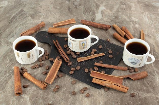 Espresso coffee, cinnamon sticks and coffee beans on marble surface