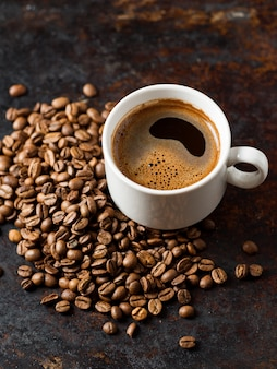 Espresso coffee cup and roasted beans on old rusty brown background