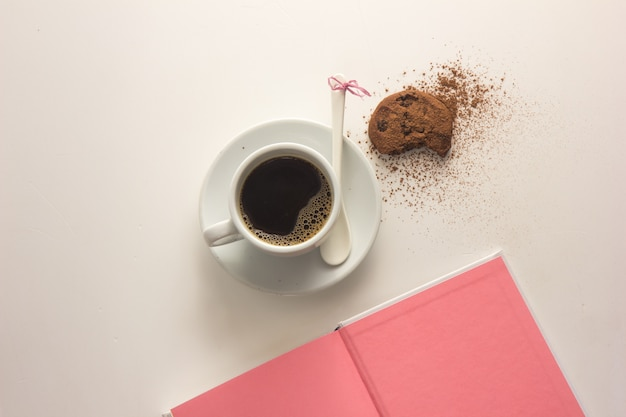 テーブルの上の本とエスプレッソコーヒーカップ。