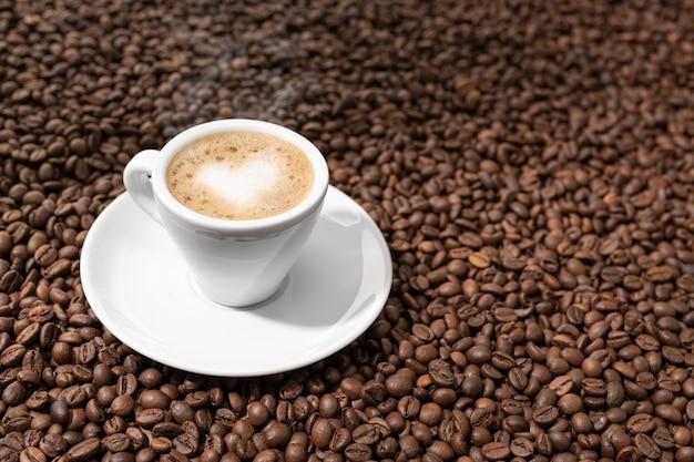 焙煎豆の背景にハート型のエスプレッソコーヒーカップ。コピースペース