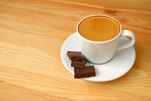 Espresso coffee and dark chocolate cubes served on wooden table