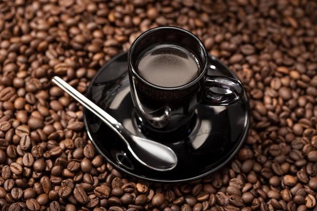 Эспрессо кофе в черной чашке и жареные бобы. кофейный фон