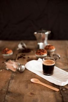 Espresso coffee in glass on white napkin with cocoa shaker and wooden spoon