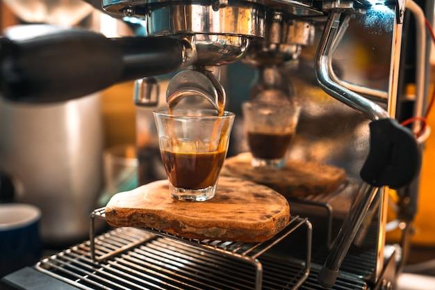 에스프레소 커피가 샷 컵으로 흘러 들어갑니다.