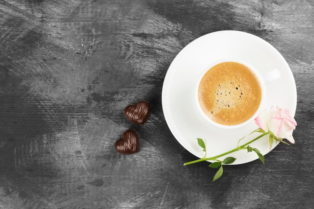 Espresso coffee in a white cup, a pink rose and chocolates on a dark background. top view, copy space. food background