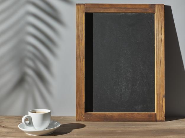 회색 벽 근처에 있는 에스프레소 컵과 분필 보드