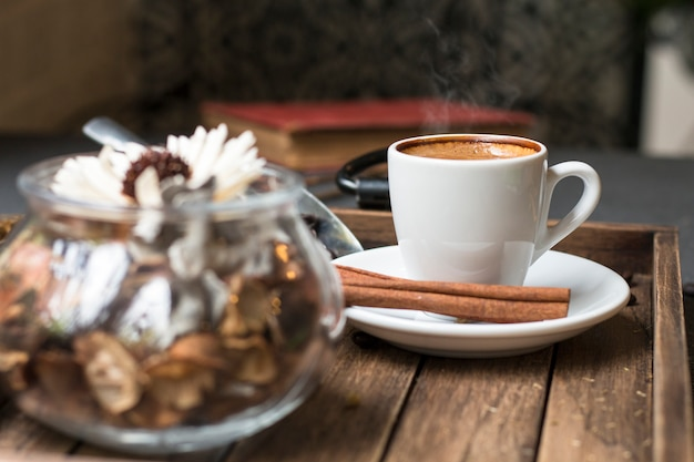 Espresso cup, coffee bean, cinnamon and dried flowers jar on wooden tray.