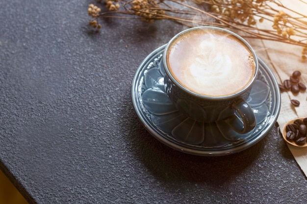 Espresso cup, latte, coffee bean and dried flowers jar on wooden.