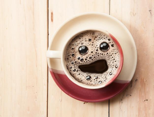 エスプレッソカップ、木製のテーブルに笑顔の顔、オーバーヘッドビュー