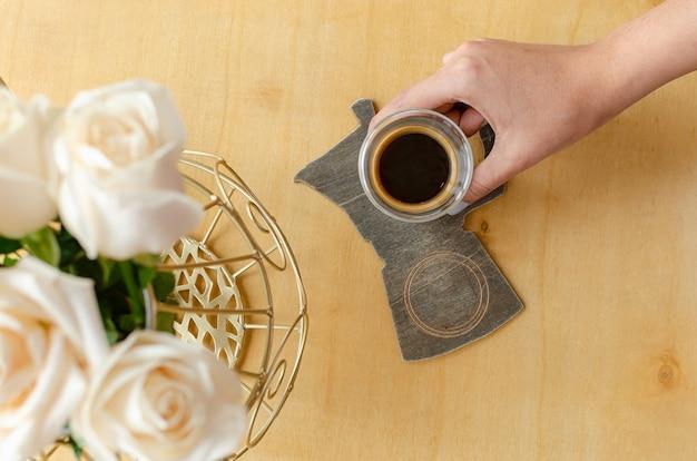 Эспрессо, ручной и с розами на деревянном столе