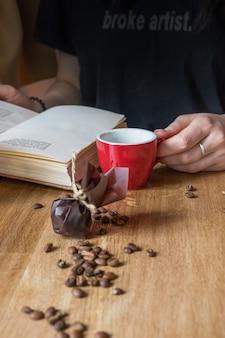 赤いカップの本とコーヒーを飲む甘い女性のエスプレッソ