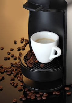 Эспрессо-машина и чашка кофе на коричневой поверхности