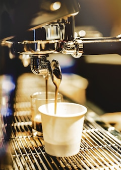 Espresso machine brewing a coffee. coffee pouring into glasses in coffee shop, espresso pouring from coffee machine